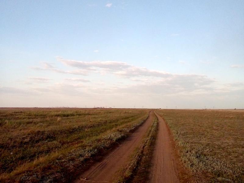 20160518. Степная дорога от посёлка Кенжеколь к павлодарскому электролизному заводу; постройки завода виднеются на горизонте.