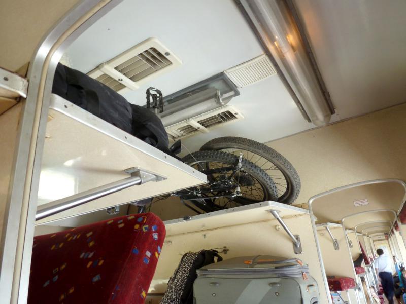 20160805. Велосипед со снятыми колёсами на третьей багажной полке плацкартного железнодорожного вагона.
