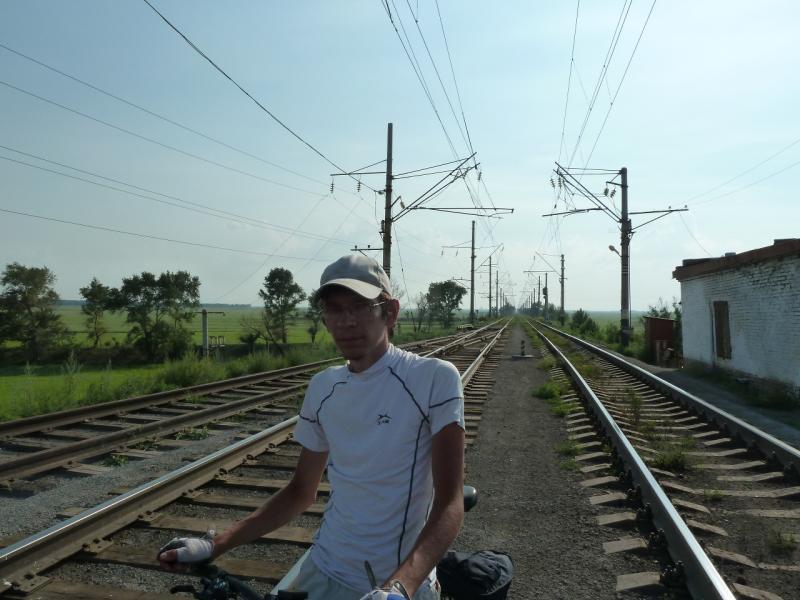 20120715. Аксу-Павлодар: Илья на фоне группы стрелок, регулирующих движение у железнодорожного моста.