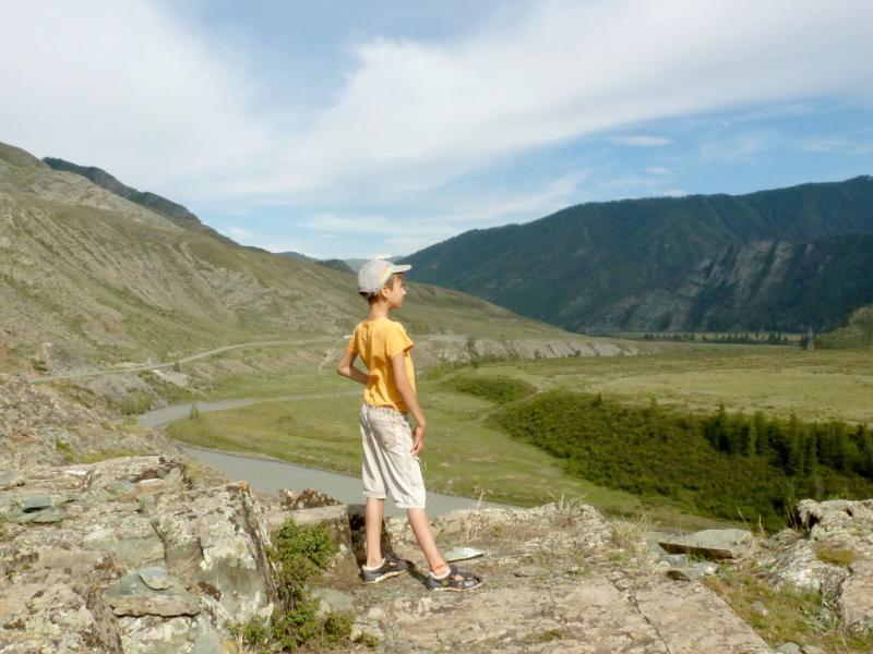 20180807. Сына позирует на скале Калбак-Таш с видом в долину, где сливаются реки Чуя и Атакты.