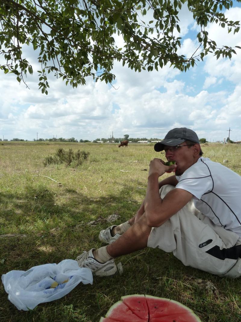 20120808. Илья поглощает арбуз, сидя под одиноким деревом у села Пушкино.