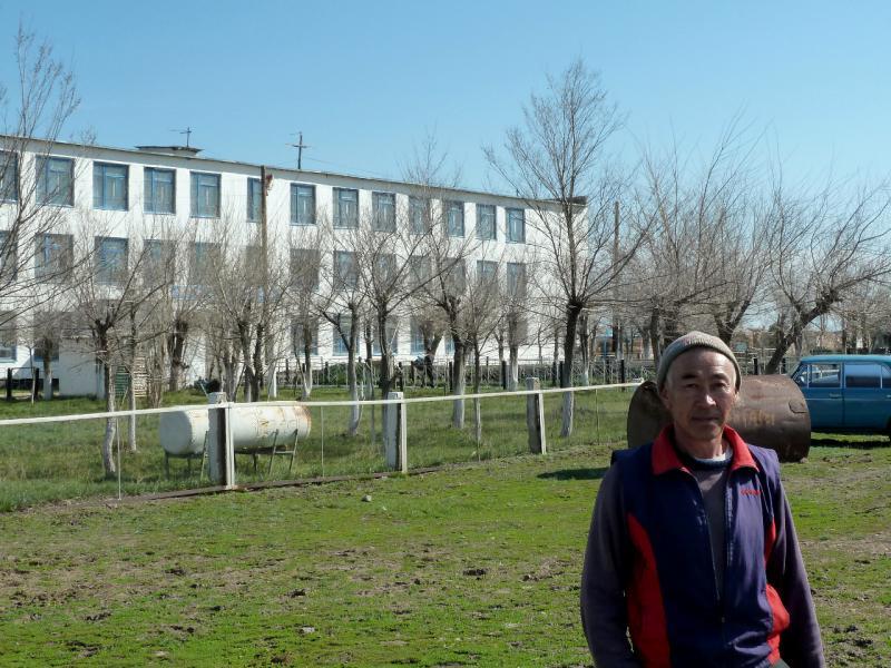 20130426. Житель села Южное Тиманай на фоне здания школы.