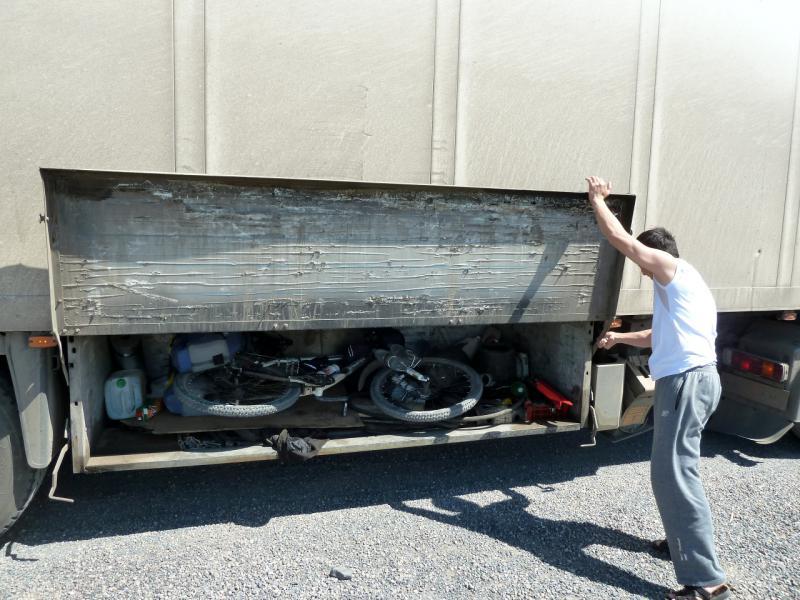20130509. Аюп устраивает мой велосипед в багажном отсеке фуры.