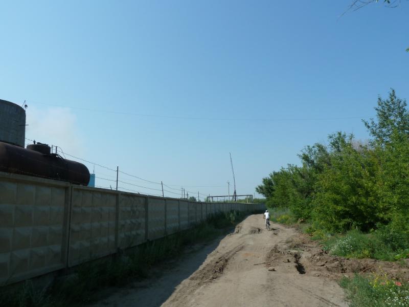 20120715. Павлодар-Аксу: едем вдоль забора промышленной зоны посёлка Аксу.