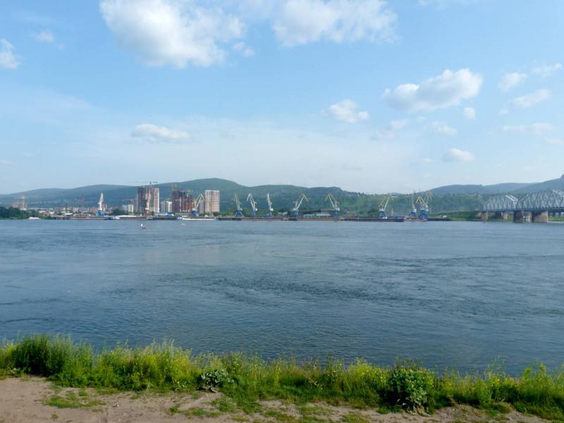 20200701. Красноярск. Вид на правый берег Енисея, с грузовым речным портом в центре и железнодорожным мостом Транссибирской магистрали справа.